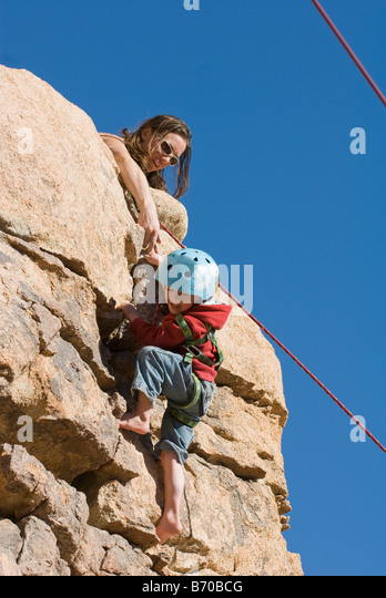 Mother helping child finish a rock climb, Joshua Tree National Park, California. - Stock Image