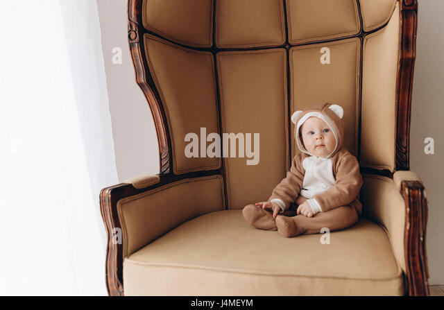 Caucasian baby boy sitting in armchair wearing bear costume - Stock-Bilder