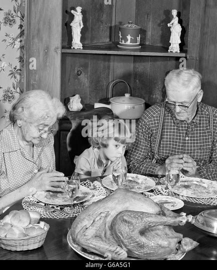 1950s FAMILY THANKSGIVING DINNER PRAYING GIRL AND GRANDPARENTS - Stock Image