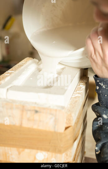 Liquid plaster flowing from bucket to a brimming mold. - Stock Image