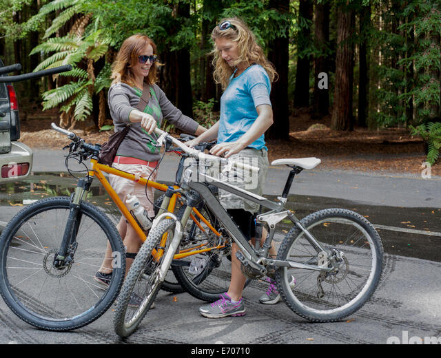 Two women mountain bikers preparing to cycle in forest - Stock-Bilder
