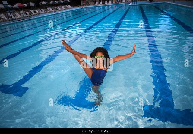 Portrait of girl standing on one leg in swimming pool wearing goggles, leg raised, looking at camera, smiling - Stock Image