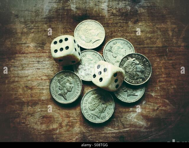 Dice and British coins - Stock Image