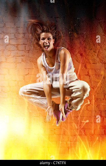 Young woman dancer jumping. With fire effect. - Stock Image