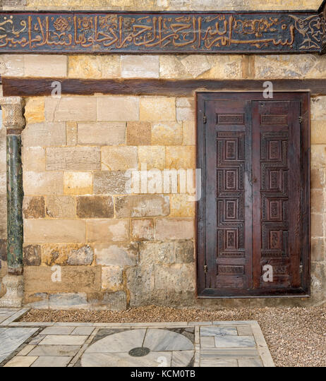 Wooden ornate door over stone wall at the Mausoleum of al-Salih Nagm Ad-Din Ayyub, Cairo, Egypt - Stock Image