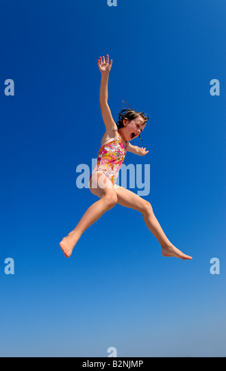 Joyful girl jumping. - Stock Image