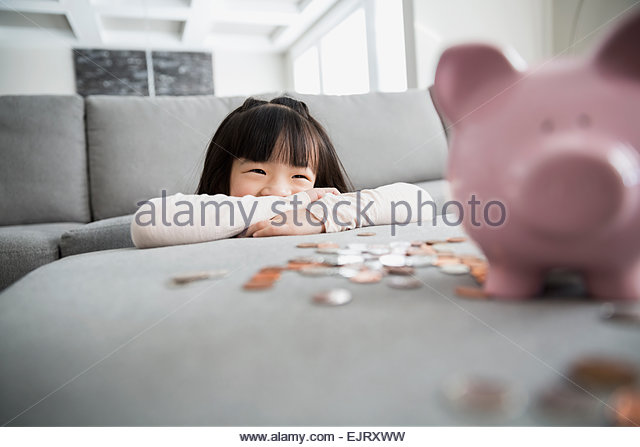 Smiling girl with piggy bank and coins - Stock-Bilder