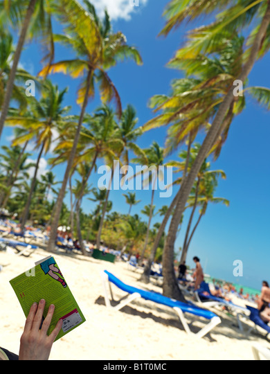 Dominican Republic Punta Cana Bavaro Beach person reading book under palm trees on white sandy beach facing the - Stock Image