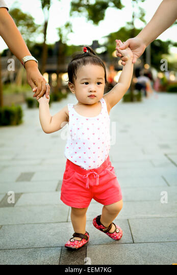 Girl (2-3) walking while adults hold her hands - Stock Image