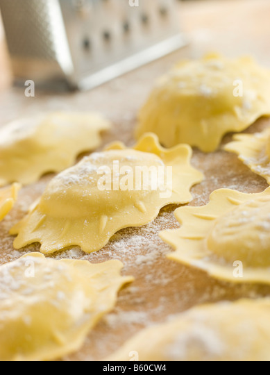 Uncooked Spinach and Ricotta Ravioli on a floured surface - Stock Image