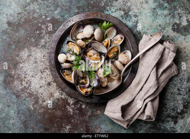 Shells vongole venus clams in metal dish on metal background - Stock Image