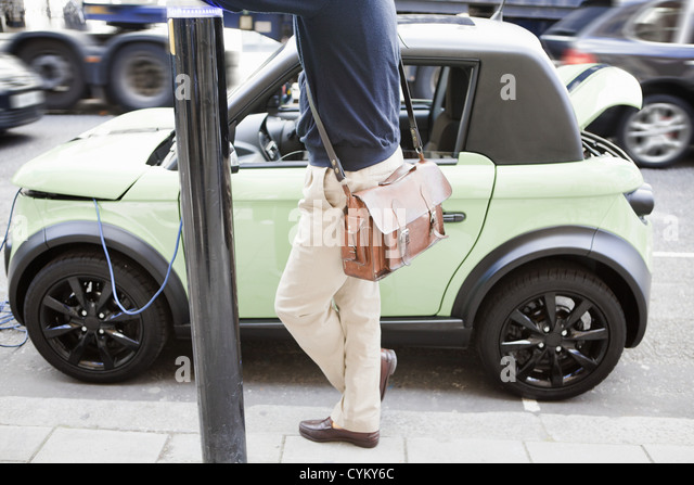 Man charging electric car on city street - Stock Image