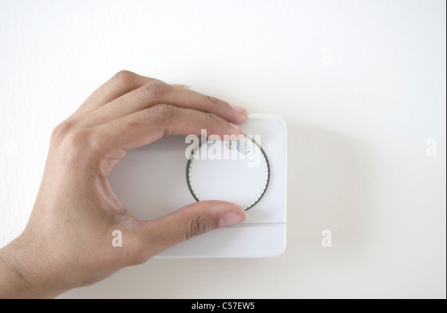 Woman adjusting climate control - Stock Image