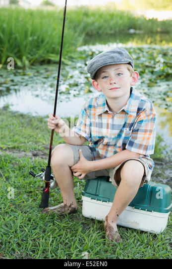 A young boy with his fishing road, by a lake or river. - Stock Image
