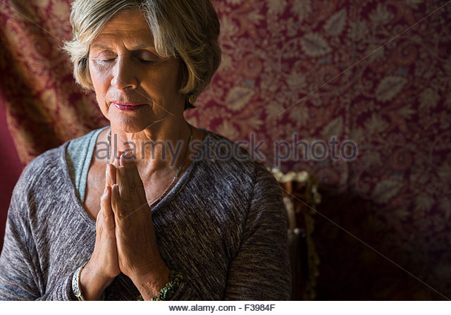 Close up senior woman meditating with eyes closed - Stock Image