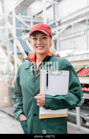 Portrait smiling worker with clipboard in food processing plant - Stock-Bilder