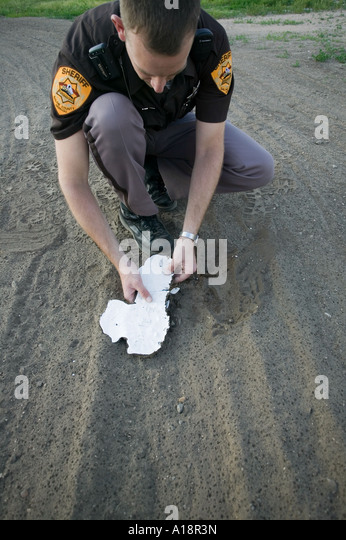 Deputy sheriff carefully lifting a plaster cast of a shoe print from the ground - Stock Image