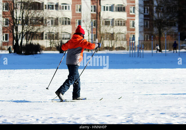 child goes skiing on the inner court of the school during physical education classes - Stock Image