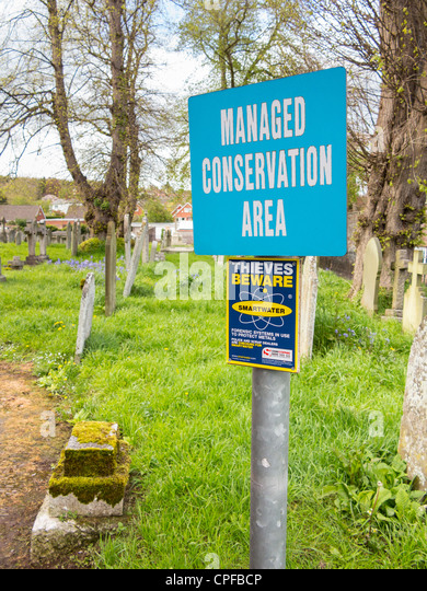Church yard in Devon displaying Thieves Beware Smartwater sign and Conservation Area sign - Stock Image