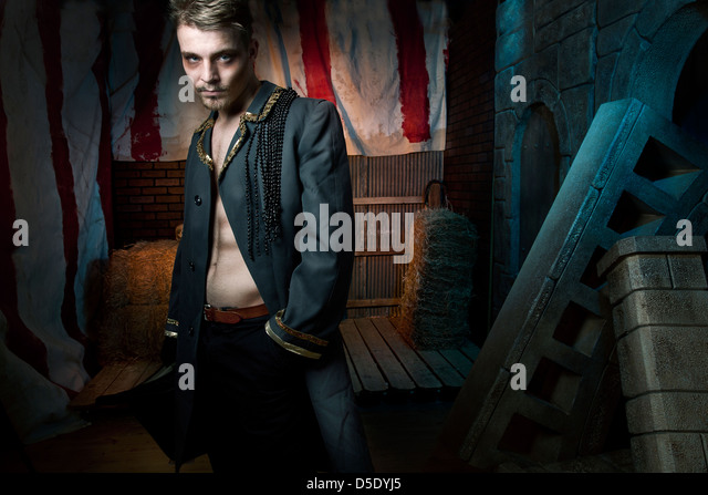 Man in long trench coat in front of dark tented alley - Stock Image