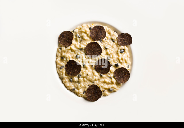 Risotto with Black Truffle on a white plate. - Stock Image