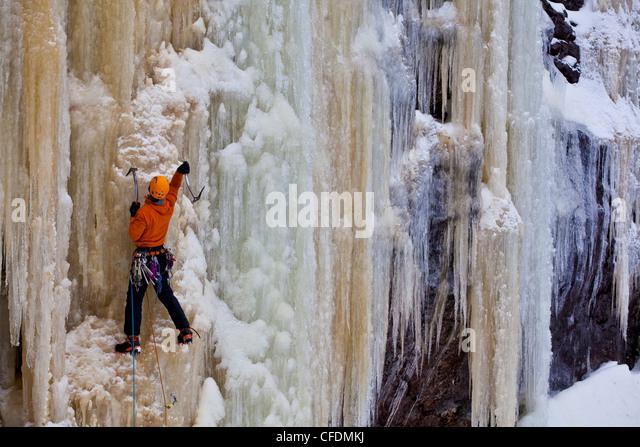A man climbs a steep, colorful ice climb, Aurorae WI 4+, near St. Raymond, Quebec, Canada - Stock Image
