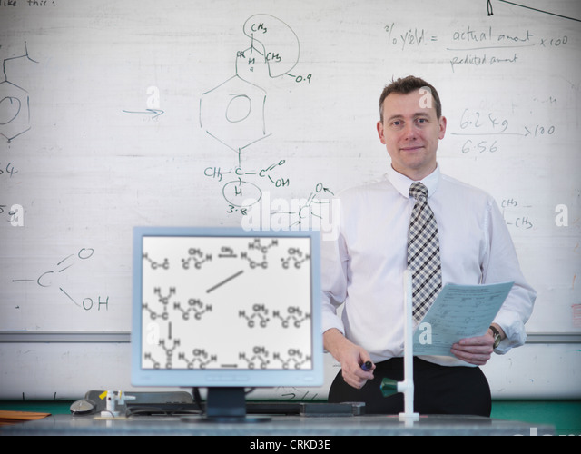 Science teacher at desk with computer - Stock Image