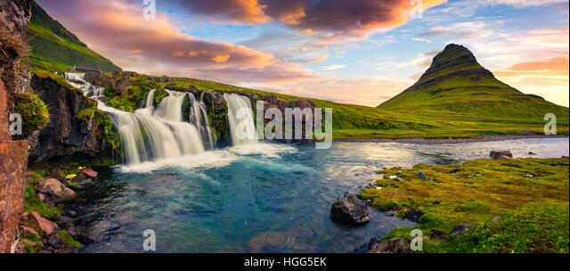 Summer sunset on famous Kirkjufellsfoss Waterfall and Kirkjufell mountain. Colorful evening panorama of Snaefellsnes - Stock Image