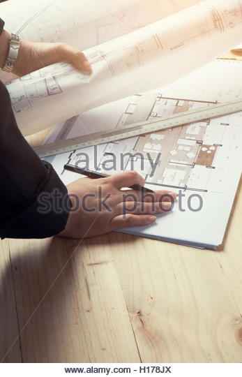 Close-up hand Of male Architect Drawing Blueprint on work space wooden table in offfice ,cross process and soft - Stock Image