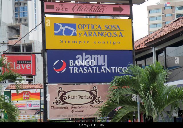 Panama Panama City Marbella shopping strip business sign signage Spanish language advertise optical store Petit - Stock Image