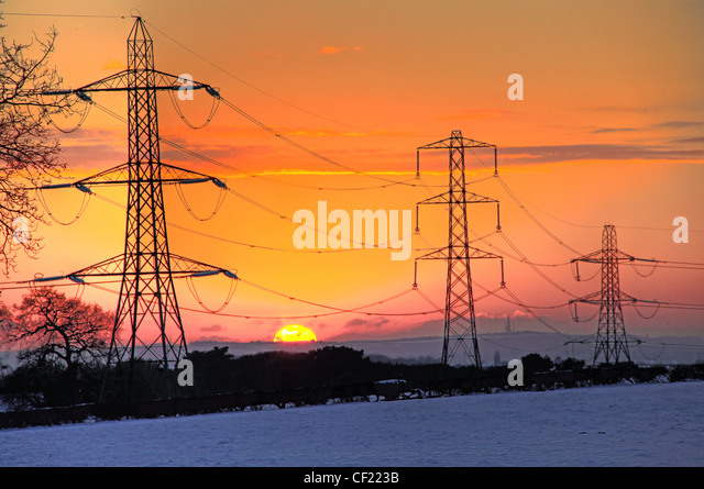 Snowy winter Cheshire power lines Sunset - Stock Image