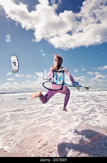 Kitesurfer running into the sea. Tarifa, Costa de la Luz, Cadiz, Andalusia, Spain, Europe. - Stock Image