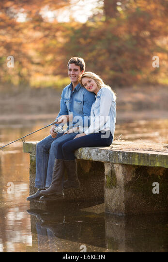 happy young man and his girlfriend fishing on pier - Stock Image