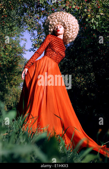 Fantasy. Artistic Stylized Woman in Trendy Red Dress and Big Frizzy Wig - Stock Image