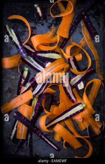 Purple and Orange Carrots, Shaved, on Dark Tray - Stock Image