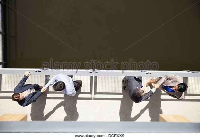 Top view of business people shaking hands on bridge - Stock Image
