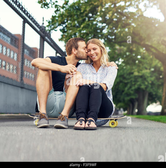 Man kissing woman on her cheek while sitting in a park - Stock Image