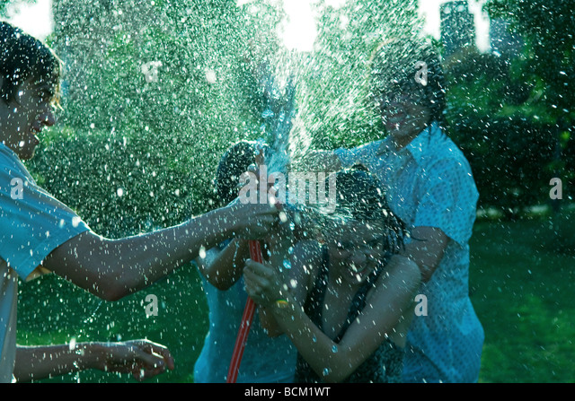Young friends having water fight with garden hose - Stock Image