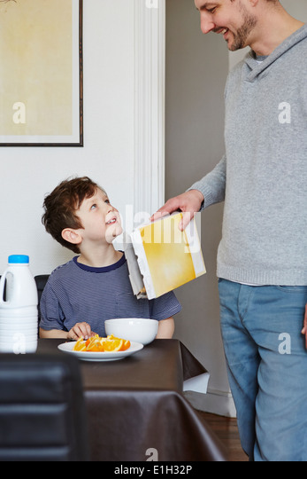 Father pouring cereal into son's bowl - Stock Image