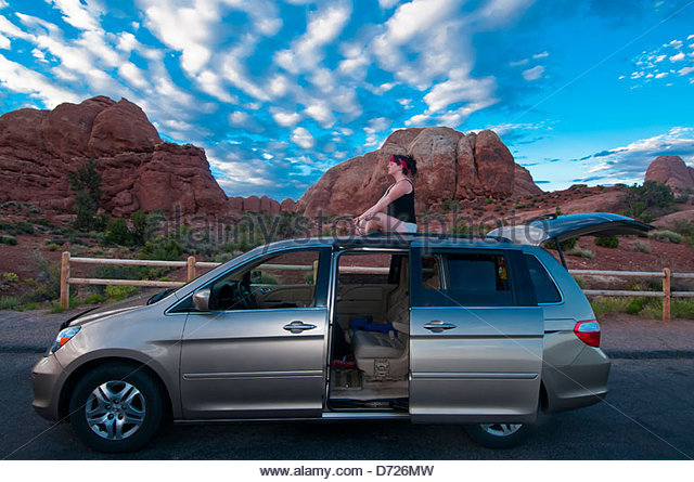 15 year old teenage girl enjoying the sunset from atop a minivan, Arches National Park, near Moab, Utah, USA - Stock Image