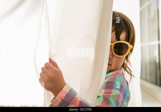 Girl peering round curtain wearing sunglasses - Stock Image