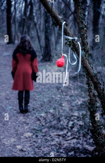 an old red balloon hanging on a branch, in a distance a woman in a red coat - Stock Image