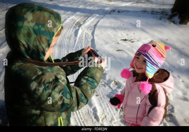 Brother Photographing Sister On Snow Covered Field - Stock Image
