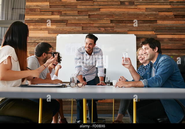 Group of happy young people having a business meeting. Creative people sitting at table in boardroom with man explaining - Stock-Bilder