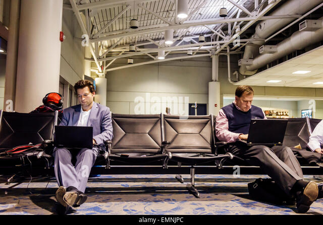 North Carolina Charlotte Charlotte Douglas International Airport CLT terminal concourse gate area man laptop using - Stock Image
