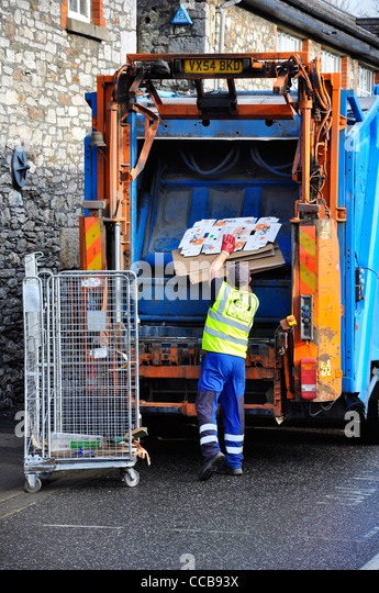 Waste collection with bin man loading refuse into rubbish truck. - Stock Image