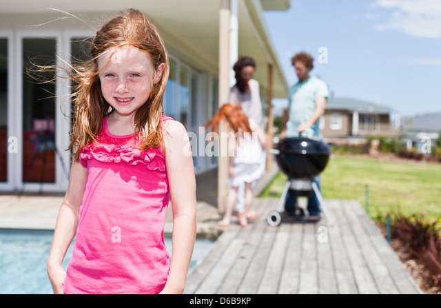 Girl smiling on backyard patio - Stock Image