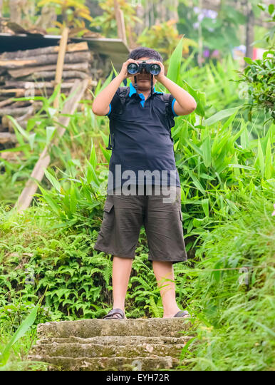 A young boy watching through binoculars with copy space, scientific activity or hobby - Stock Image