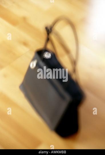 Purse on floor, blurred - Stock Image