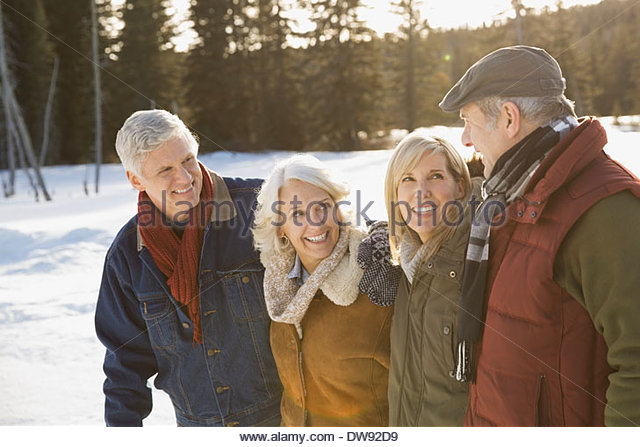 Smiling mature friends standing outdoors in winter - Stock Image